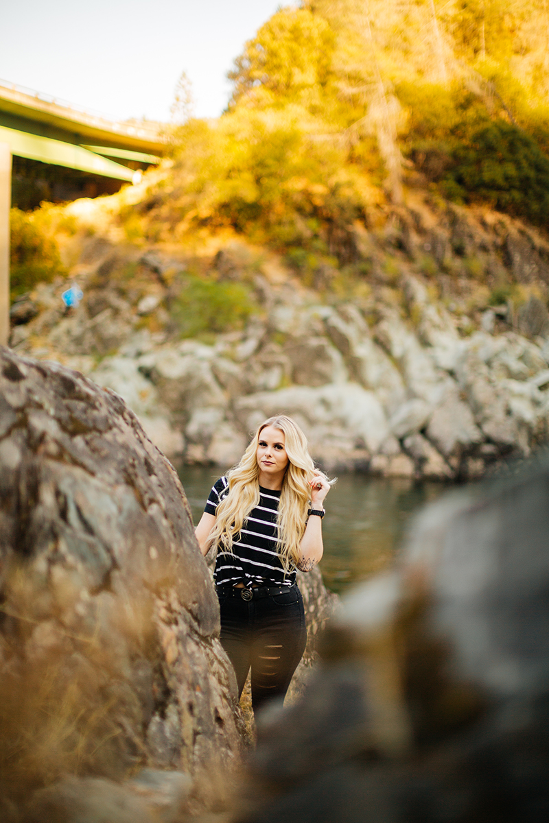 A beautiful young blonde woman poses for an Auburn boudoir photography near the North Fork American River next to rocks wearing black ripped jeans and a black striped shirt.