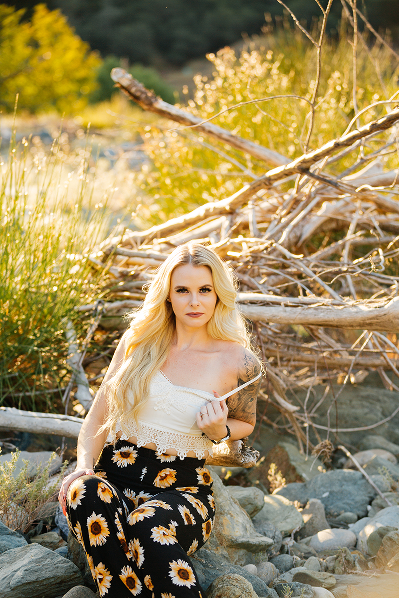 A beautiful young blonde woman poses for an Auburn boudoir photography near the North Fork American River sitting on a rock in front of branches and tall grass wearing a white tank top and a black sunflower skirt