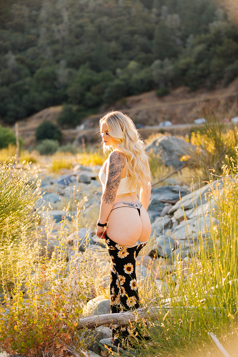 A beautiful young blonde woman poses for an Auburn boudoir photography near the North Fork American River standing in front of tall grass on the shore wearing a white tank top and pulling down her black sunflower skirt showing black underwear