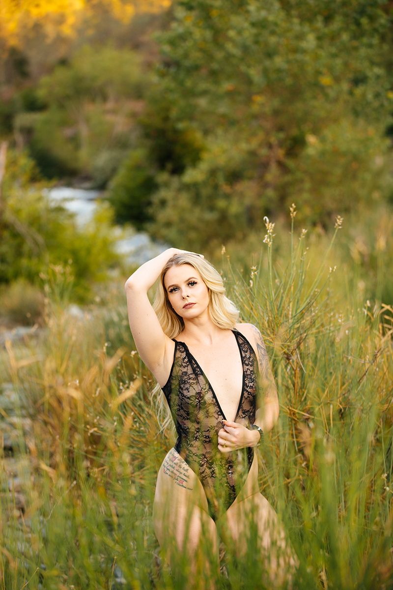 A beautiful young blonde woman poses for an Auburn boudoir photography near the North Fork American River standing in front of tall grass on the shore wearing a black lingerie body suit