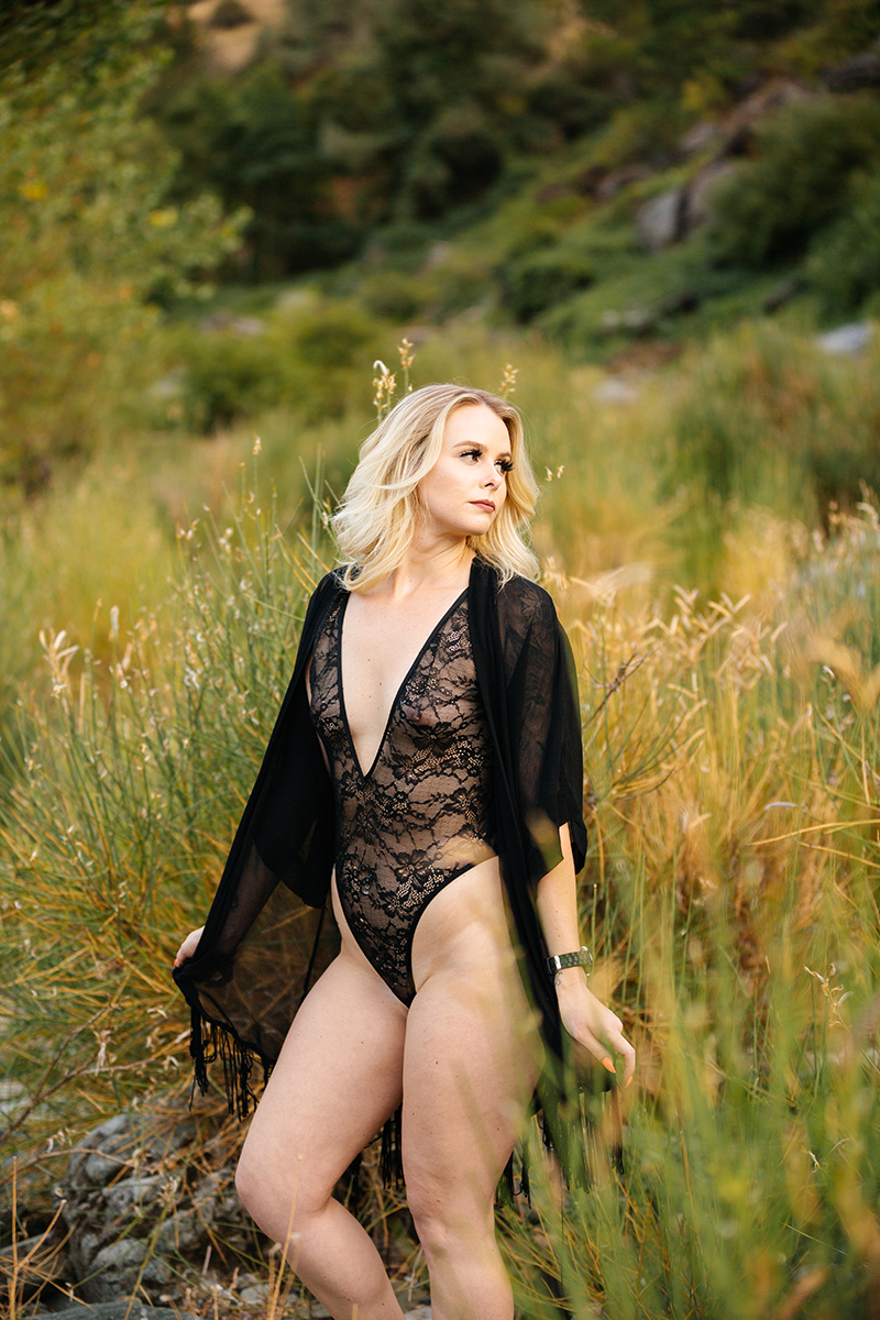 A beautiful young blonde woman poses for an Auburn boudoir photography near the North Fork American River standing in front of tall grass on the shore wearing a black lingerie body suit and a black robe