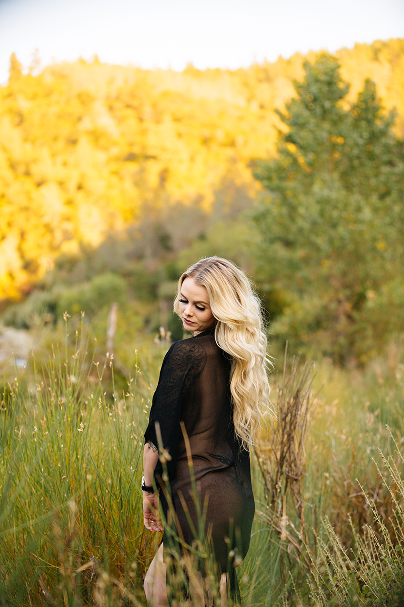 A beautiful young blonde woman poses nude for an Auburn boudoir photography near the North Fork American River standing in front of tall grass on the shore wearing a black robe