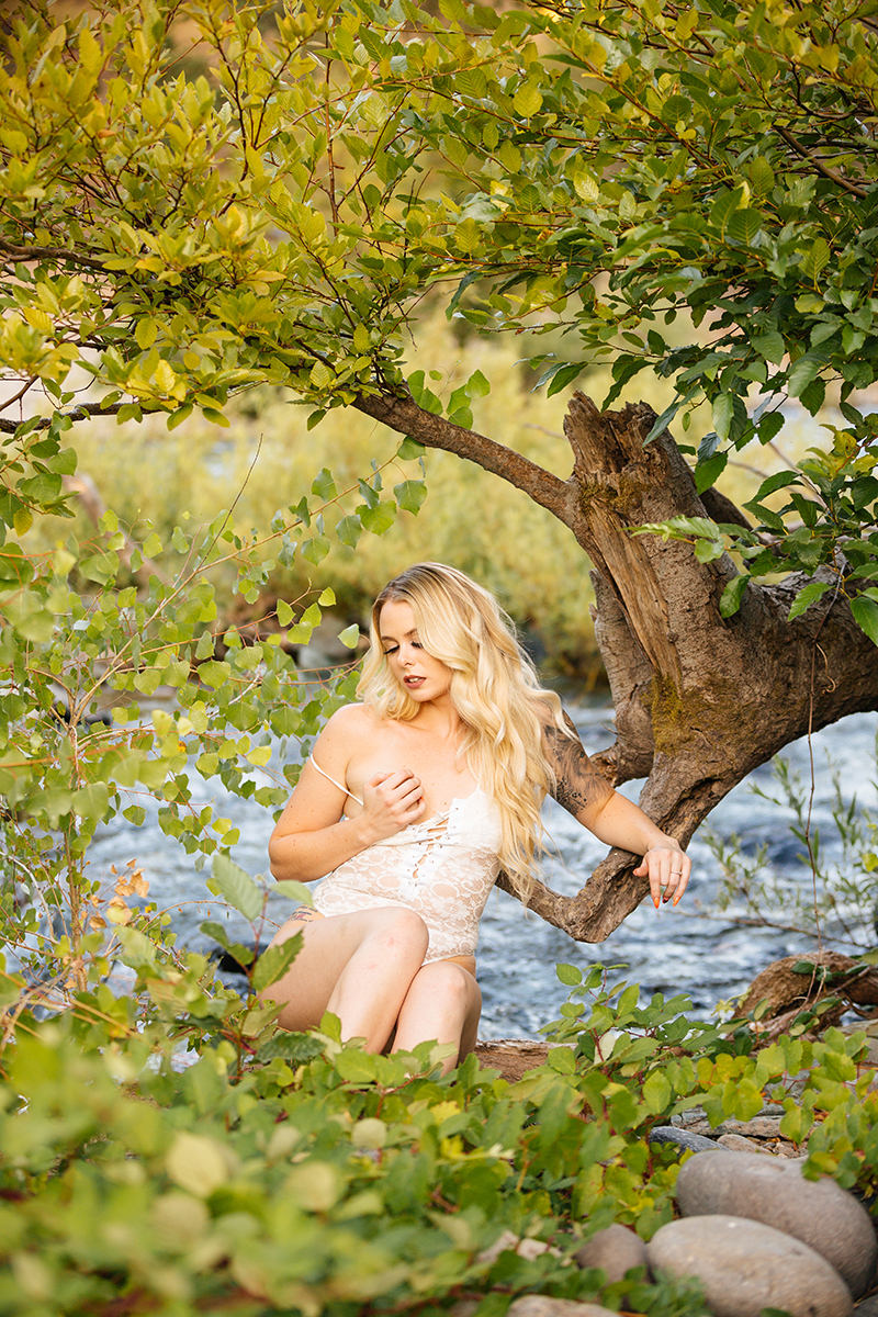 A beautiful young blonde woman poses for an Auburn boudoir photography near the North Fork American River standing in front of trees and bushes on the shore wearing a white lingerie body suit