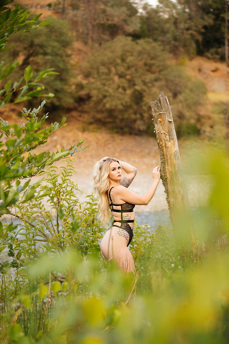 A beautiful young blonde woman poses for an Auburn boudoir photography near the North Fork American River leaning on a tree on the shore wearing a black lingerie body suit