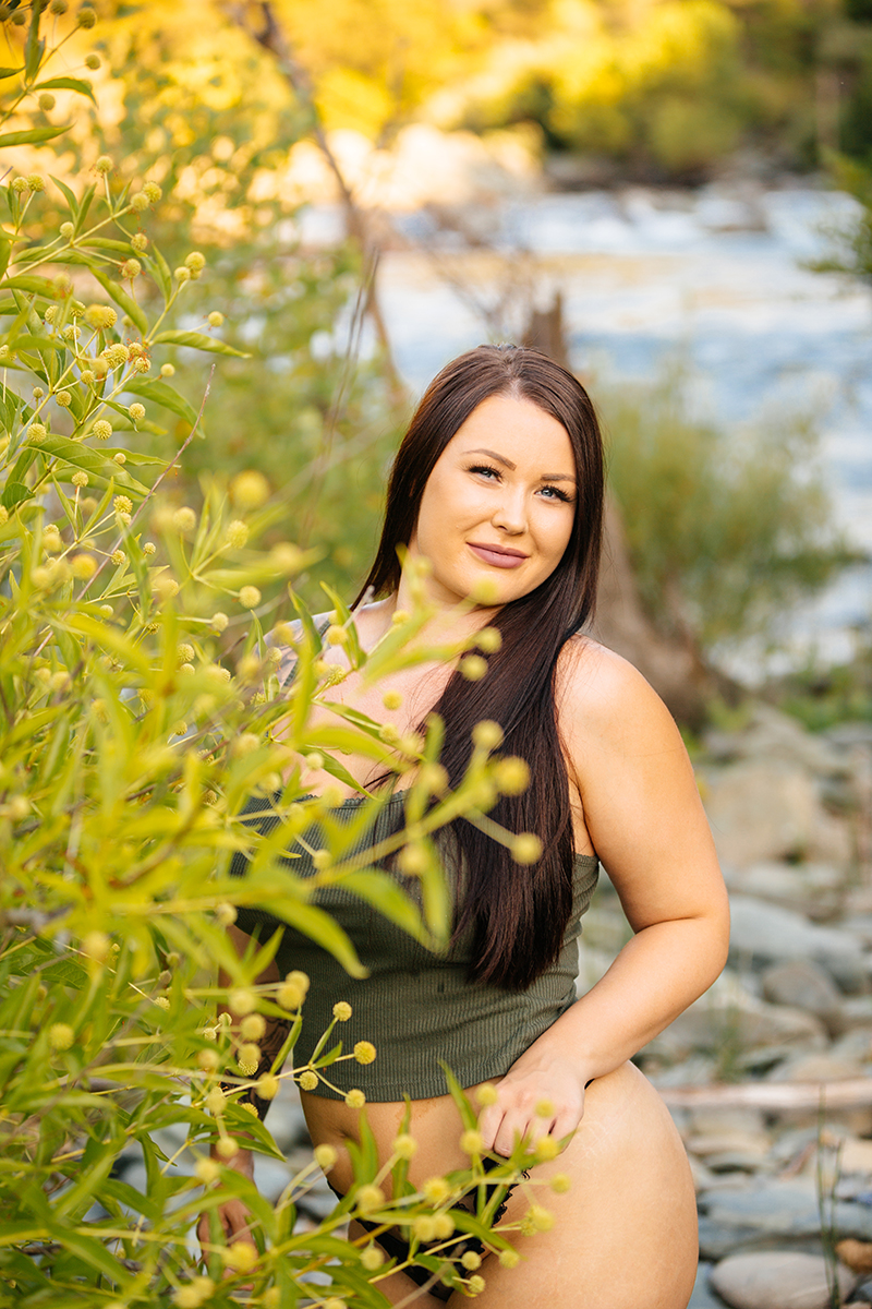 A beautiful brunette woman poses for an Auburn boudoir photography session near Sacramento, California next to a river on rocks surrounded by bushes wearing a green tank top and black lace underwear