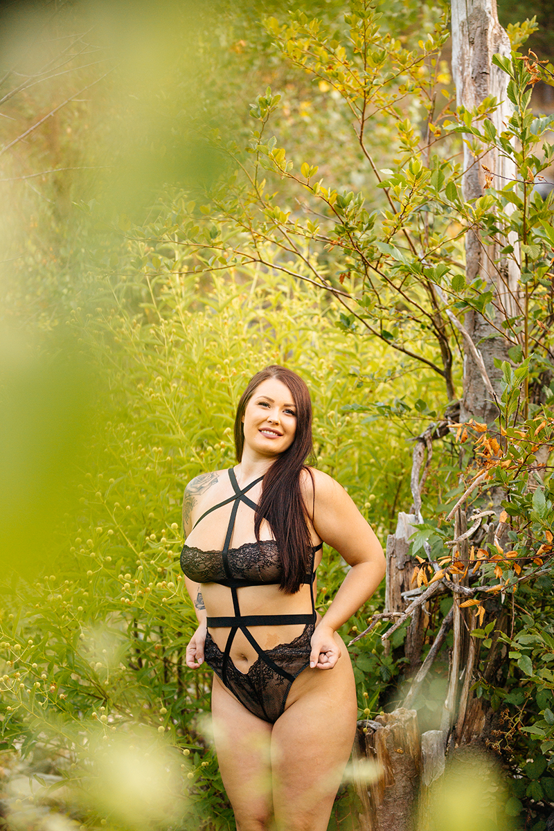 A beautiful brunette woman poses for an Auburn boudoir photography session near Sacramento, California next to a river on rocks surrounded by bushes wearing a black lace lingerie body suit