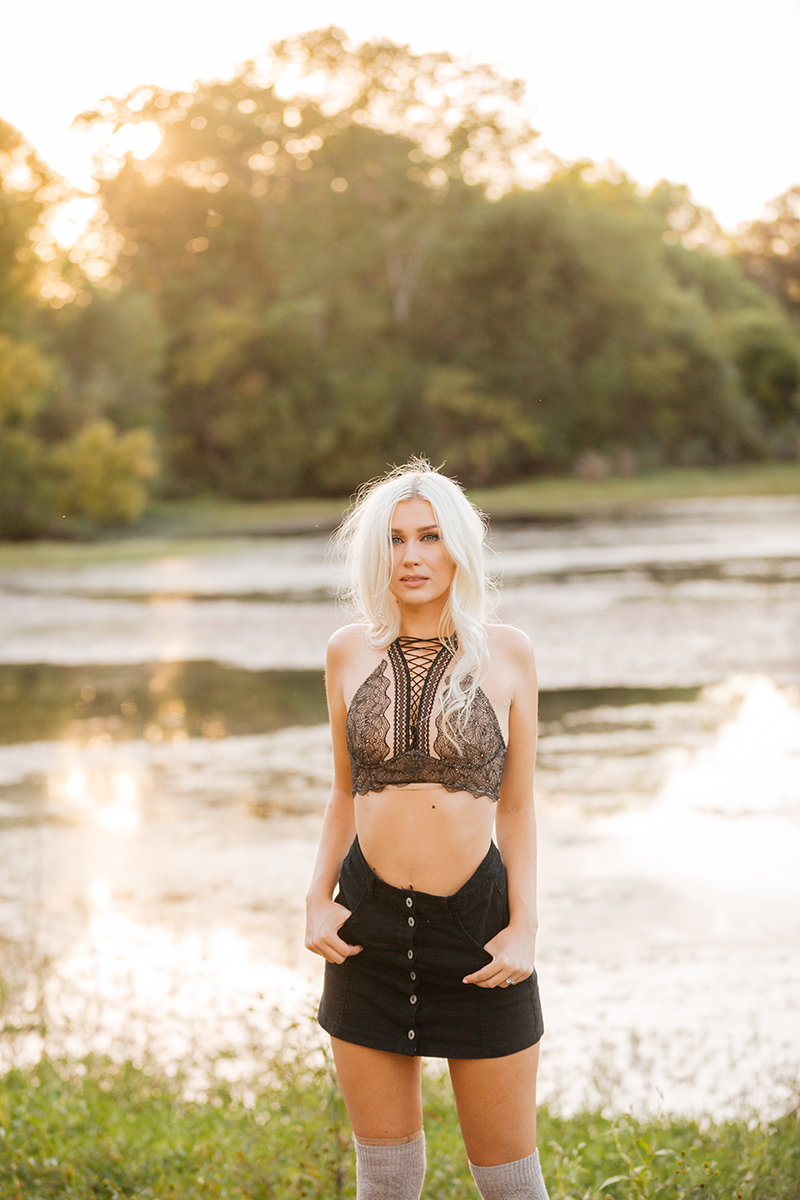 A beautiful young blonde woman poses for Horseshoe Road Recreation Area boudoir photos wearing a black bra, a black skirt and tan knee high socks in a field near a pond as the sun sets behind her in Oakdale near Sacramento, California