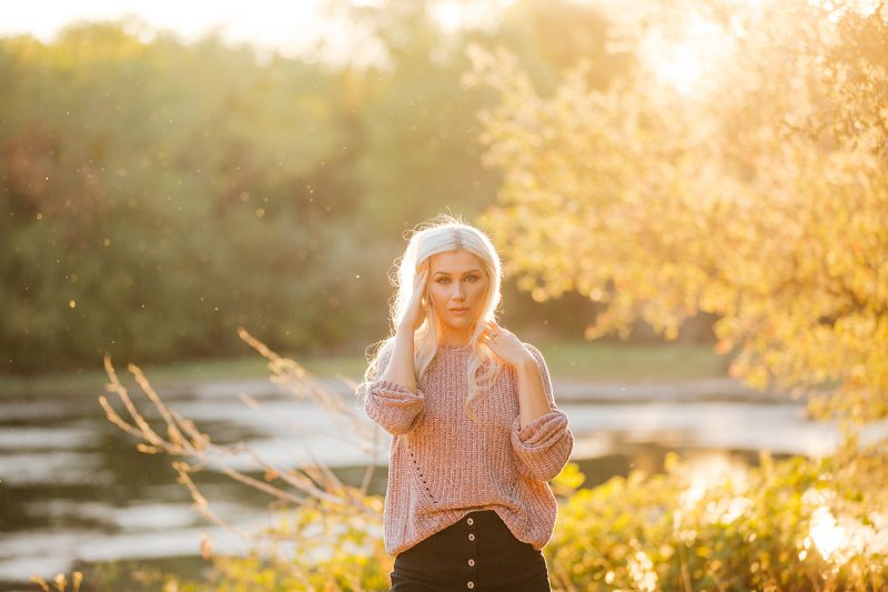 A beautiful young blonde woman poses for Horseshoe Road Recreation Area boudoir photos wearing a pink sweater, a black skirt and tan knee high socks in a field near a pond as the sun sets behind her in Oakdale near Sacramento, California