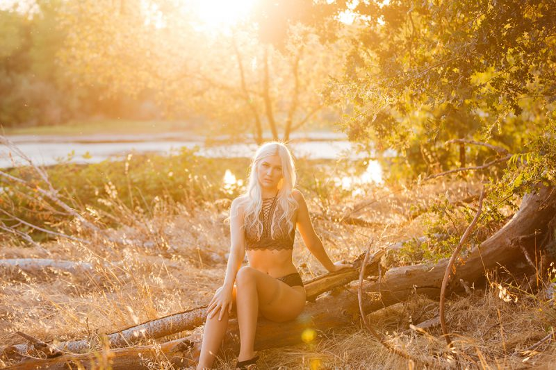 A beautiful young blonde woman sits on a log for Horseshoe Road Recreation Area boudoir photos wearing a black bra and underwear set in a field near a pond as the sun sets behind her in Oakdale near Sacramento, California