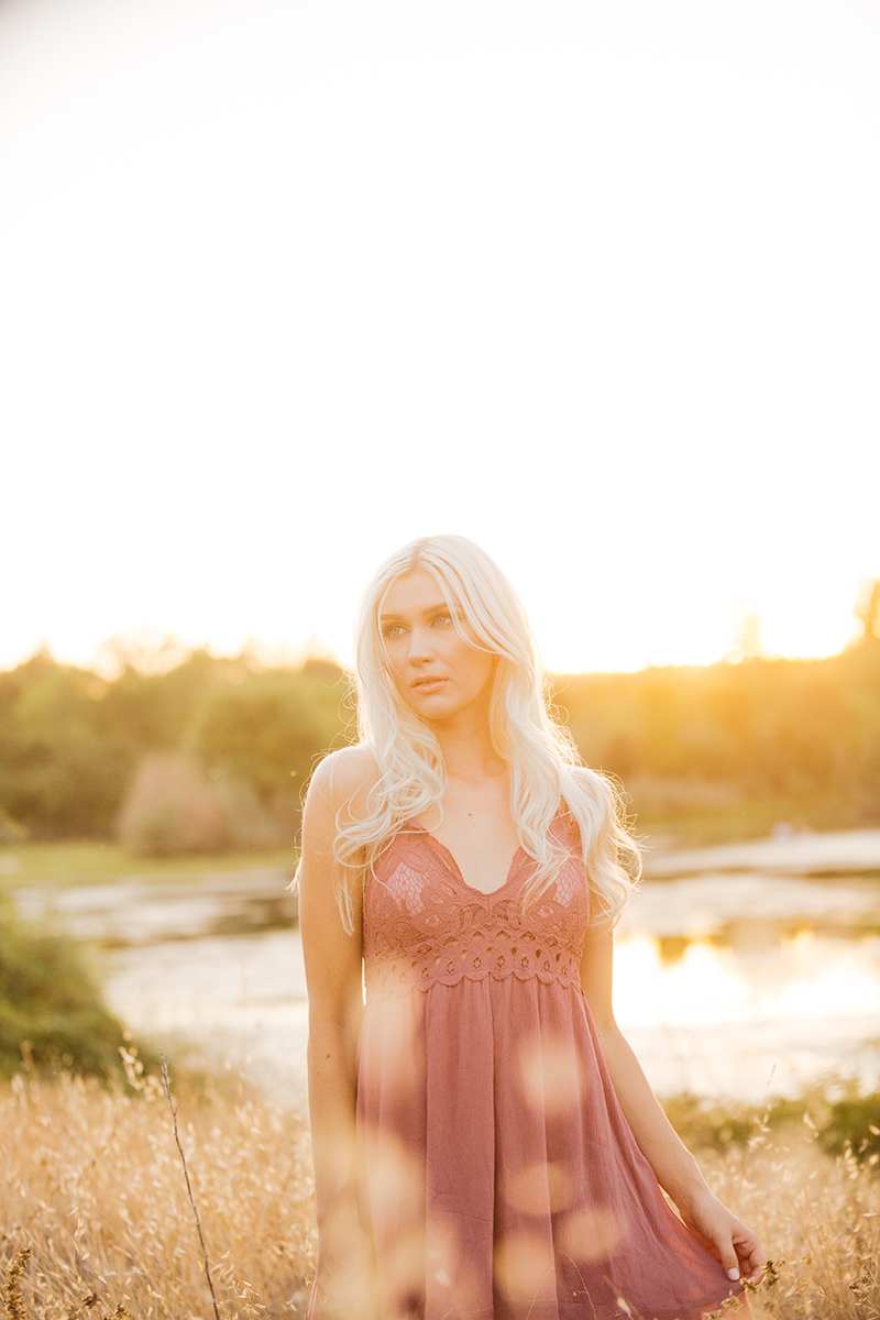 A beautiful young blonde woman poses for Horseshoe Road Recreation Area boudoir photos wearing a pink dress in a field near a pond as the sun sets behind her in Oakdale near Sacramento, California