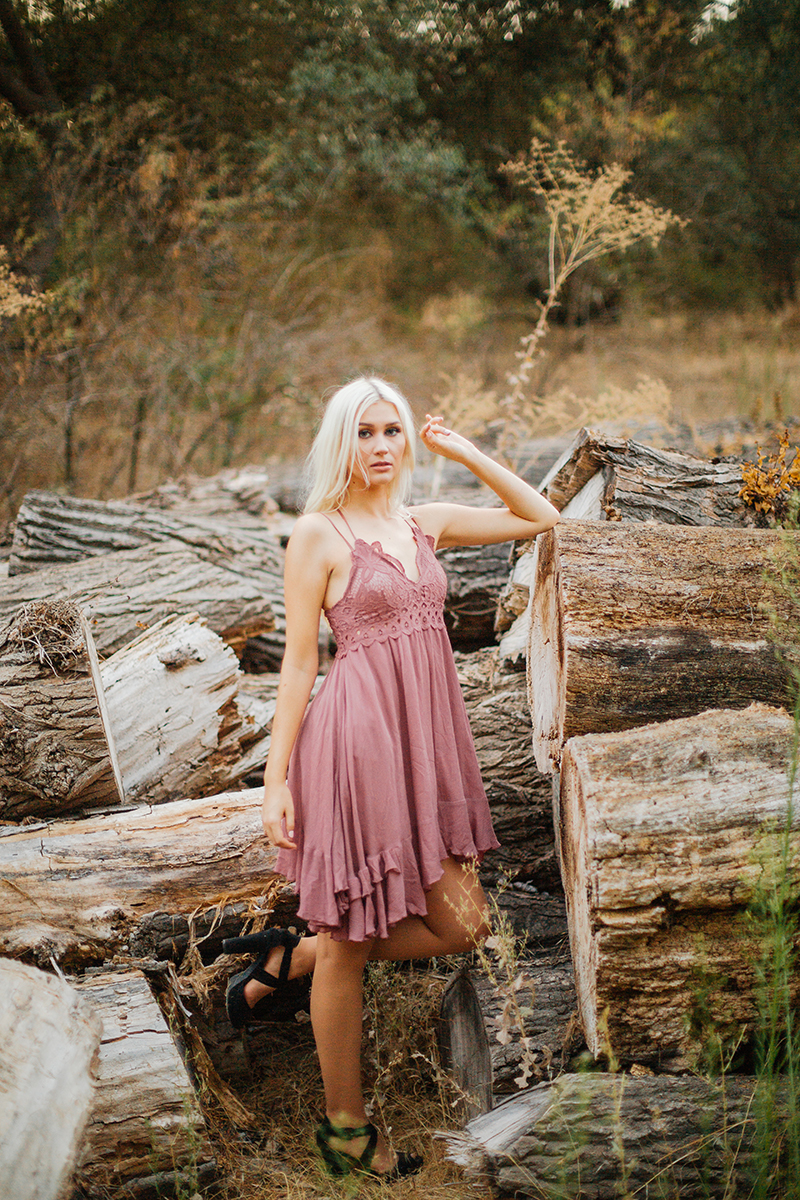 A beautiful young blonde woman poses for Horseshoe Road Recreation Area boudoir photos wearing a pink dress in a field next to wood piles in Oakdale near Sacramento, California