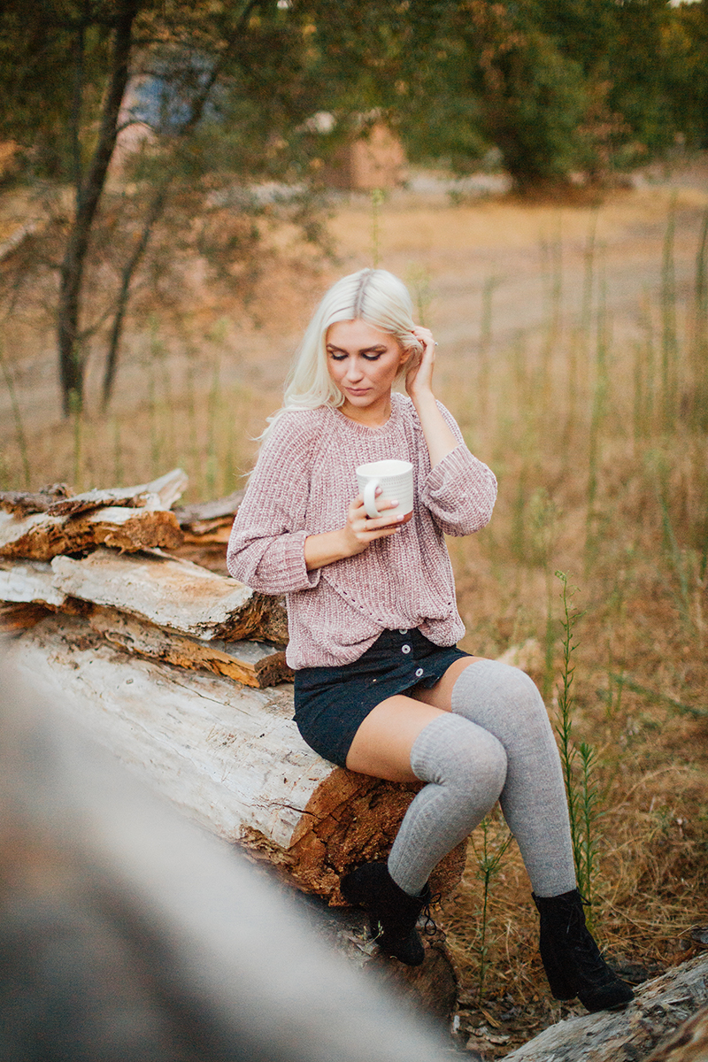 A beautiful young blonde woman poses for Horseshoe Road Recreation Area boudoir photos wearing a pink sweater, a black skirt and tan knee high socks holding a coffee mug in a field next to wood piles in Oakdale near Sacramento, California