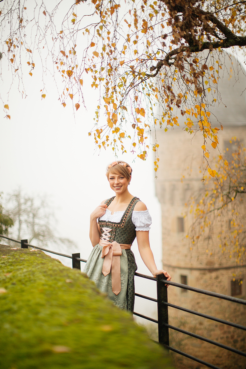 A beautiful young short haired blonde woman poses for a Burg Lichtenberg boudoir photography wearing a green and white dirdnl with a pink ribbon leaning on railing in front of a castle tower with fog in the background near Kusel, Germany