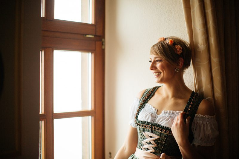 A beautiful young short haired blonde woman poses for a Burg Lichtenberg boudoir photography wearing a green and white dirdnl with a pink ribbon sitting inside at a window near Kusel, Germany