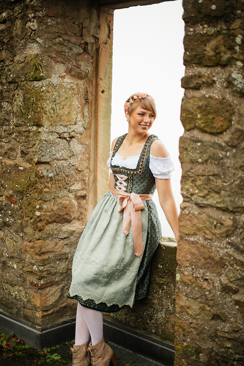 A beautiful young short haired blonde woman poses for a Burg Lichtenberg boudoir photography wearing a green and white dirdnl with a pink ribbon sitting sitting in a stone window near Kusel, Germany