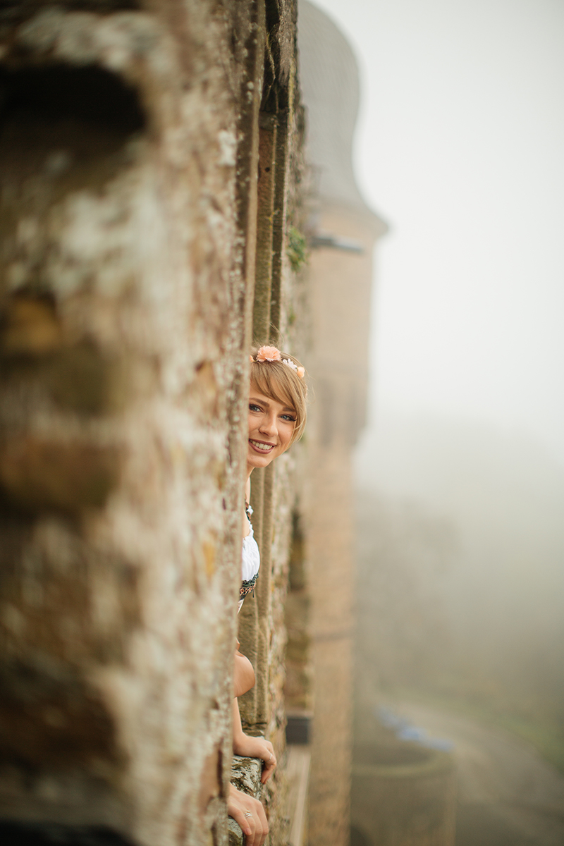 A beautiful young short haired blonde woman poses for a Burg Lichtenberg boudoir photography wearing a green and white dirdnl with a pink ribbon standing in a stone window near Kusel, Germany