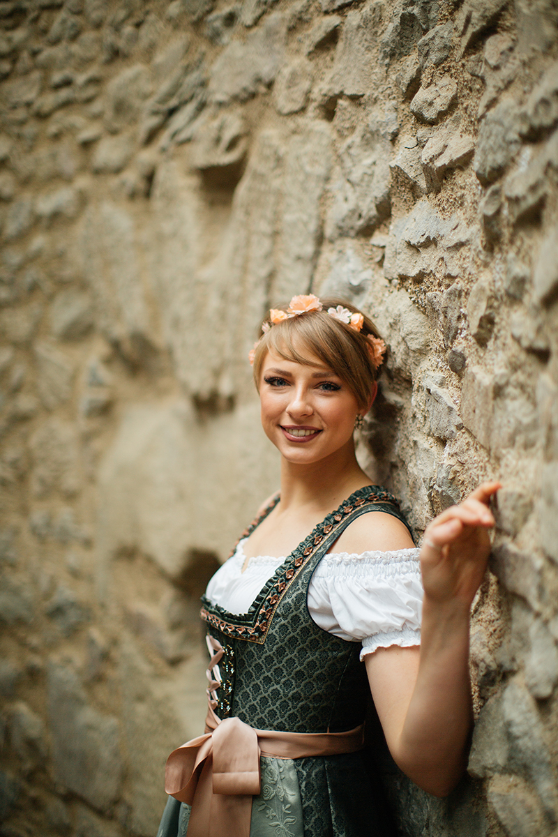 A beautiful young short haired blonde woman poses for a Burg Lichtenberg boudoir photography wearing a green and white dirdnl with a pink ribbon leaning on a stone wall near Kusel, Germany