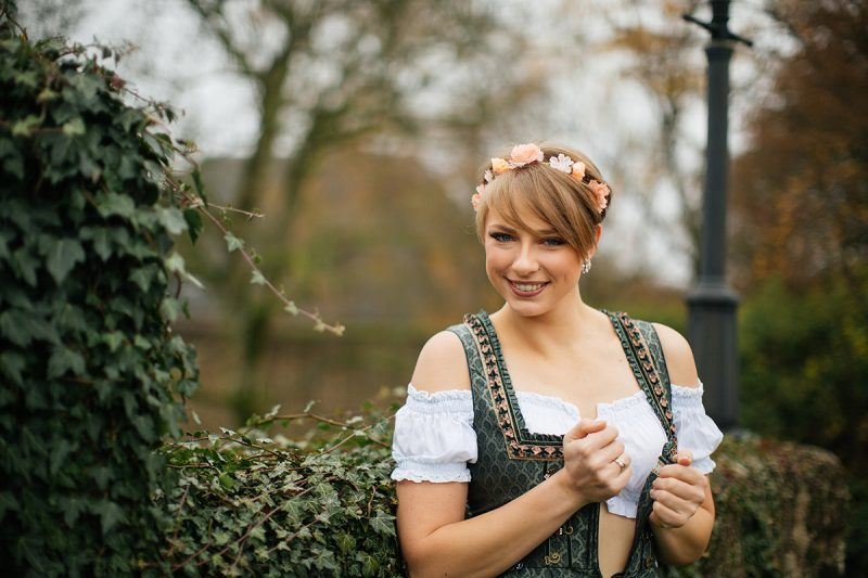 A beautiful young short haired blonde woman poses for a Burg Lichtenberg boudoir photography wearing a green and white dirdnl with a pink ribbon leaning on a stone wall covered in vines near Kusel, Germany