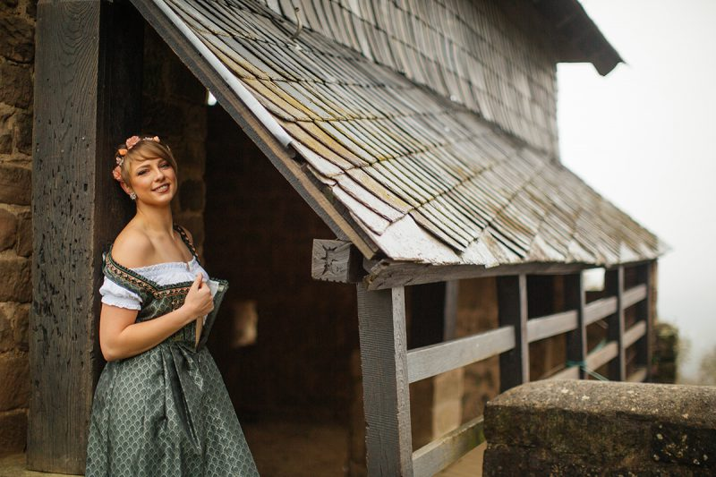 A beautiful young short haired blonde woman poses for a Burg Lichtenberg boudoir photography wearing a green and white dirdnl with a pink ribbon leaning on a brick wall under an old roof near Kusel, Germany