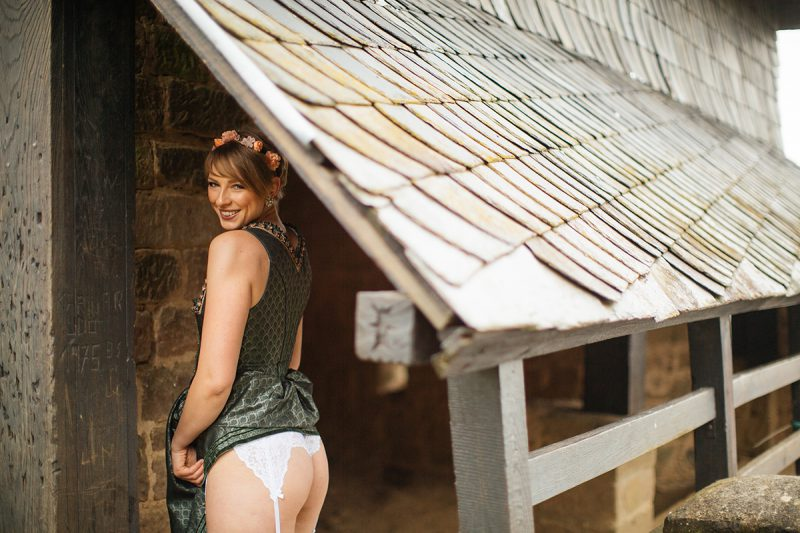 A beautiful young short haired blonde woman poses for a Burg Lichtenberg boudoir photography wearing a green and white dirdnl with a pink ribbon and white stockings leans on a brick wall under an old roof near Kusel, Germany
