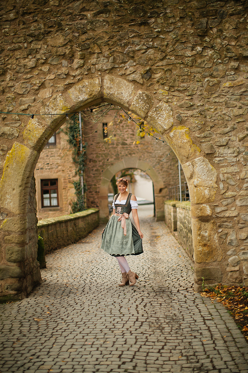 A beautiful young short haired blonde woman poses for a Burg Lichtenberg boudoir photography wearing a green and white dirdnl with a pink ribbon and white stockings stands on a cobblestone entry under a stone arch near Kusel, Germany