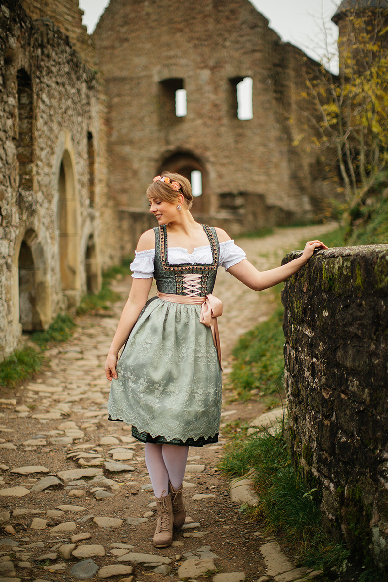 A beautiful young short haired blonde woman poses for a Burg Lichtenberg boudoir photography wearing a green and white dirdnl with a pink ribbon and white stockings standing on a cobblestone path leaning on a stone wall near Kusel, Germany