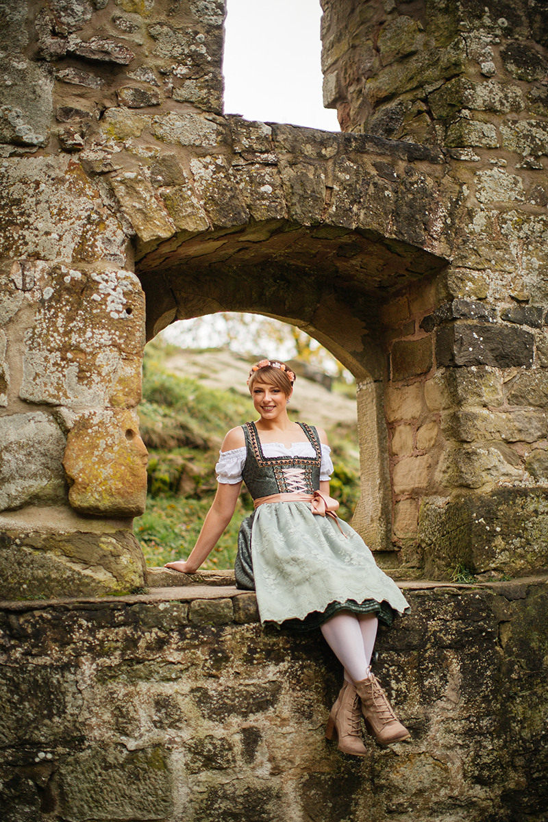 A beautiful young short haired blonde woman poses for a Burg Lichtenberg boudoir photography wearing a green and white dirdnl with a pink ribbon and white stockings sitting in a stone castle window near Kusel, Germany