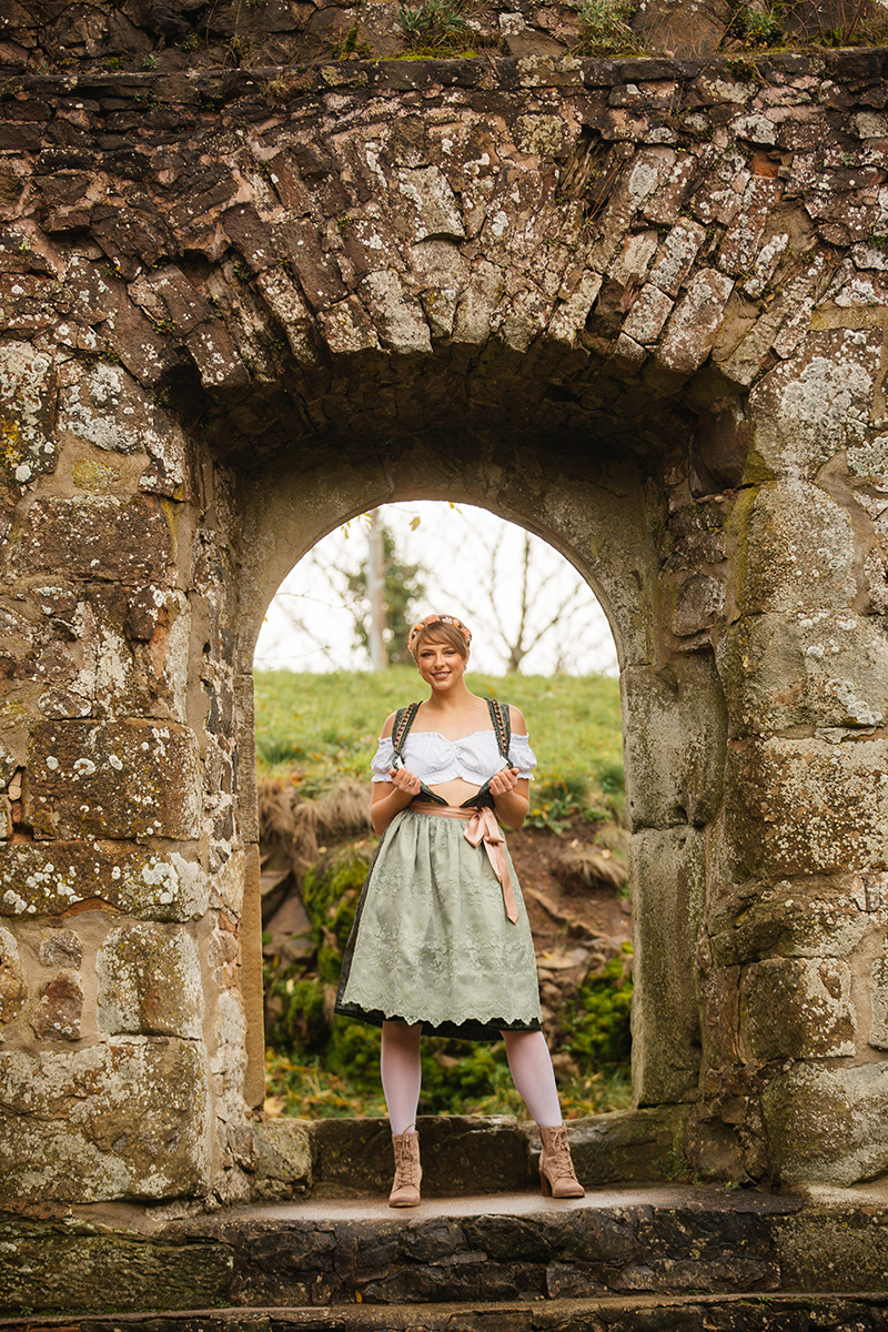 A beautiful young short haired blonde woman poses for a Burg Lichtenberg boudoir photography wearing a green and white dirdnl with a pink ribbon and white stockings standing in a stone castle window near Kusel, Germany