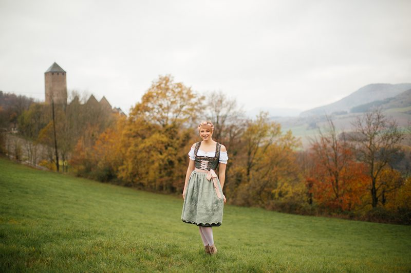 A beautiful young short haired blonde woman poses for a Burg Lichtenberg boudoir photography wearing a green and white dirdnl with a pink ribbon and white stockings standing in an open green field surrounded by trees with the castle in the background near Kusel, Germany