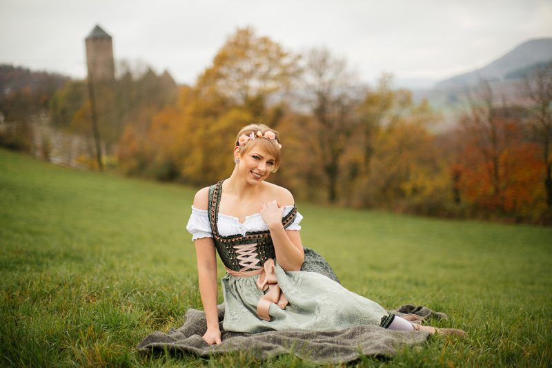 A beautiful young short haired blonde woman poses for a Burg Lichtenberg boudoir photography wearing a green and white dirdnl with a pink ribbon and white stockings sitting on a blanket in an open green field surrounded by trees with the castle in the background near Kusel, Germany
