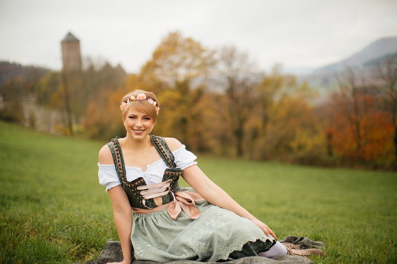 A beautiful young short haired blonde woman poses for a Burg Lichtenberg boudoir photography undoing her green and white dirdnl with a pink ribbon and white stockings sitting on a blanket in an open green field surrounded by trees with the castle in the background near Kusel, Germany