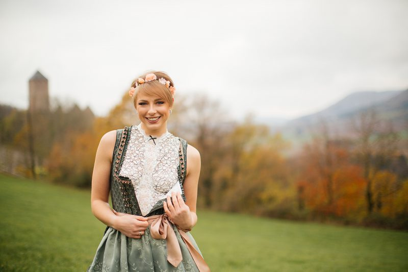 A beautiful young short haired blonde woman poses for a Burg Lichtenberg boudoir photography unzipping her green and white dirdnl with a pink ribbon and white stockings standing in an open green field surrounded by trees with the castle in the background near Kusel, Germany