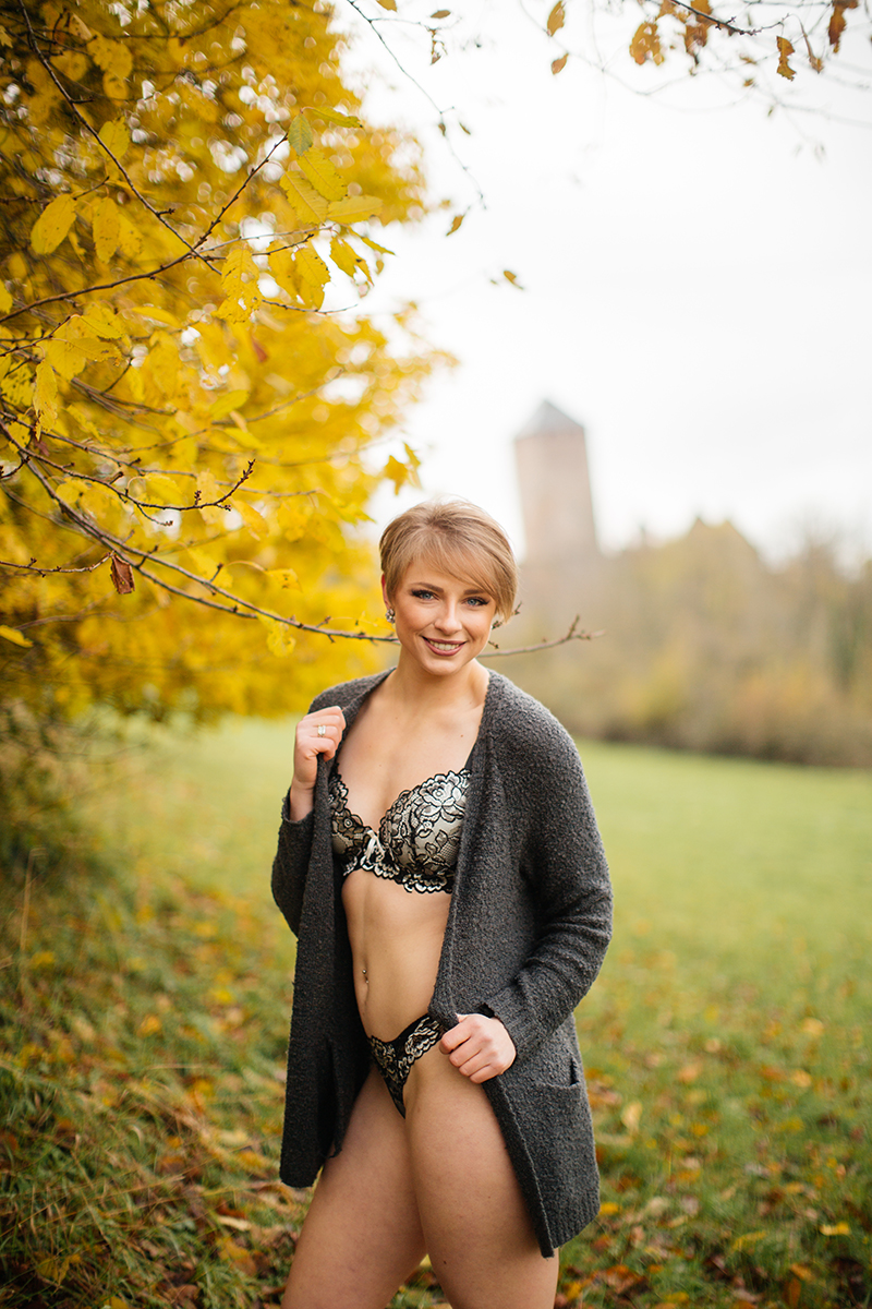 A beautiful young short haired blonde woman poses for a Burg Lichtenberg boudoir photography wearing a green bra and underwear set with a gray cardigan standing in an open green field surrounded by trees with the castle in the background near Kusel, Germany