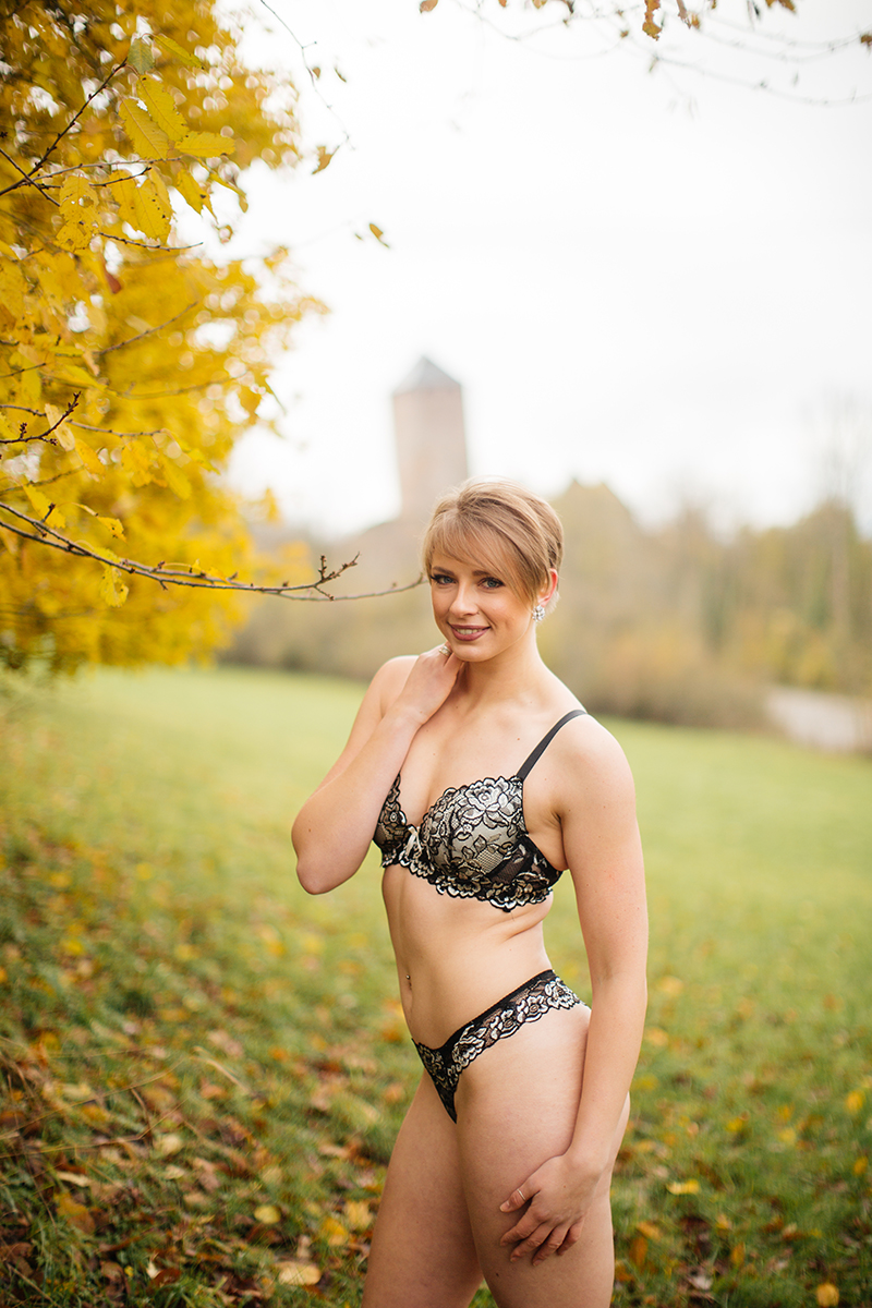 A beautiful young short haired blonde woman poses for a Burg Lichtenberg boudoir photography wearing a green bra and underwear set standing in an open green field surrounded by trees with the castle in the background near Kusel, Germany