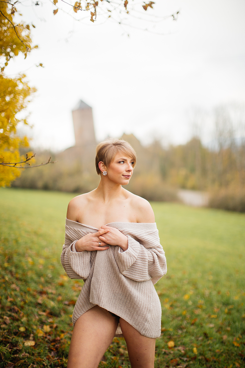 A beautiful young short haired blonde woman poses topless for a Burg Lichtenberg boudoir photography wearing a green underwear and a tan cardigan standing in an open green field surrounded by trees with the castle in the background near Kusel, Germany