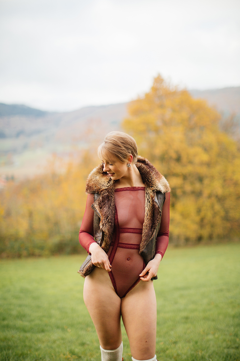 A beautiful young short haired blonde woman poses for a Burg Lichtenberg boudoir photography wearing red lingerie and a brown fur jacket standing in an open green field surrounded by trees with the castle in the background near Kusel, Germany