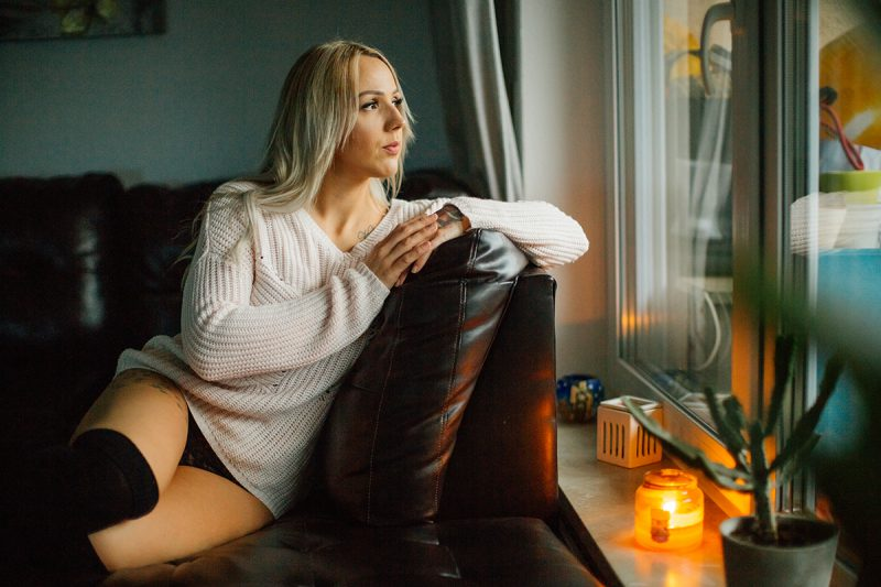A beautiful tattooed blonde German woman poses for an in-home Niedermohr boudoir photography session wearing a white sweater, a black bra and black knee high socks on a black leather couch near a window with candles lit near Kaiserslautern, Germany