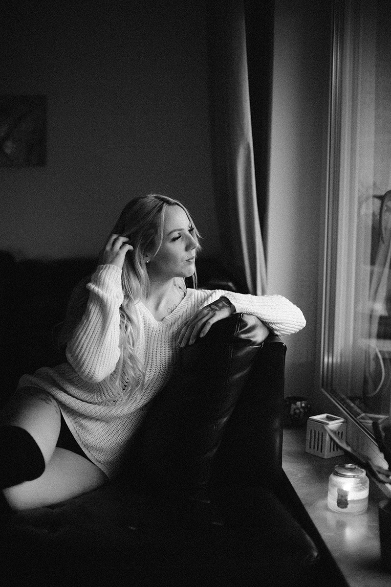 A beautiful tattooed blonde German woman poses for an in-home Niedermohr boudoir photography session wearing a white sweater, a black bra, underwear and black knee high socks on a black leather couch near a window with candles lit near Kaiserslautern, Germany