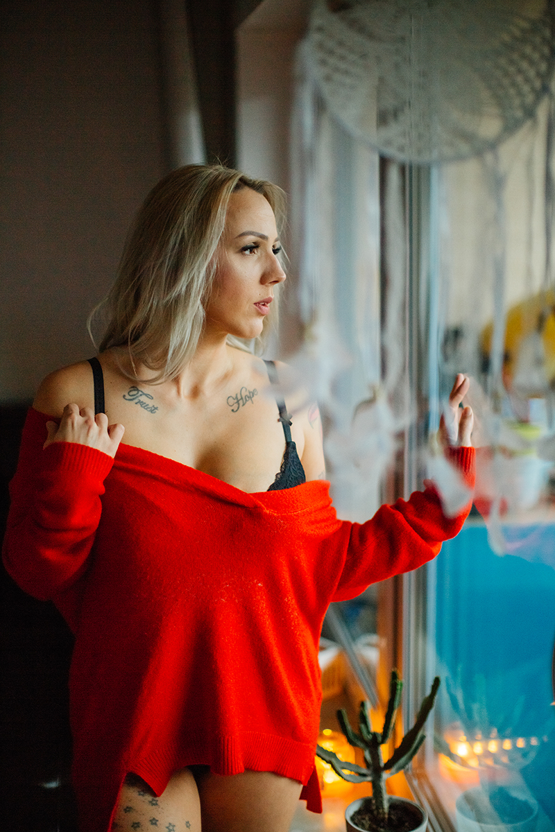 A beautiful tattooed blonde German woman poses for an in-home Niedermohr boudoir photography session wearing a red sweater, a black bra, underwear and black knee high socks in front of a black leather couch near a window with candles lit near Kaiserslautern, Germany