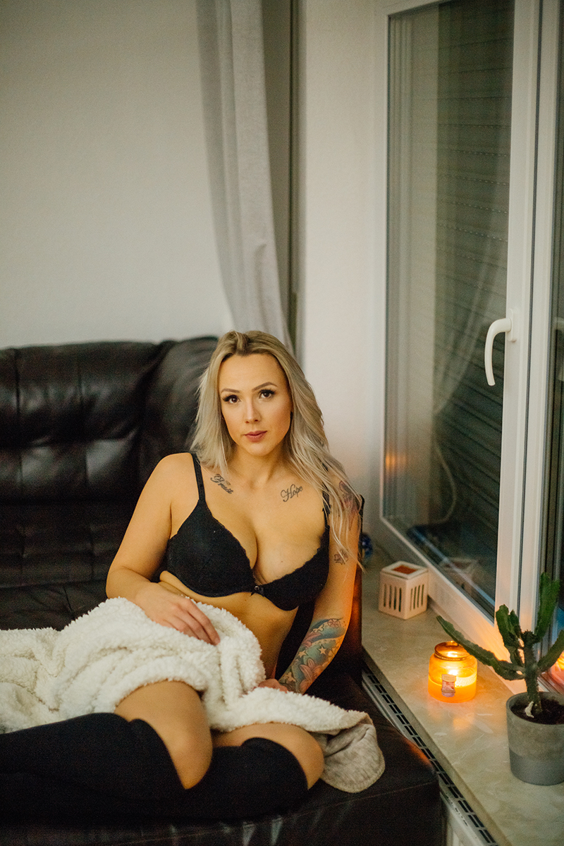 A beautiful tattooed blonde German woman poses for an in-home Niedermohr boudoir photography session wearing a black bra, underwear and black knee high socks on a black leather couch near a window with candles lit near Kaiserslautern, Germany