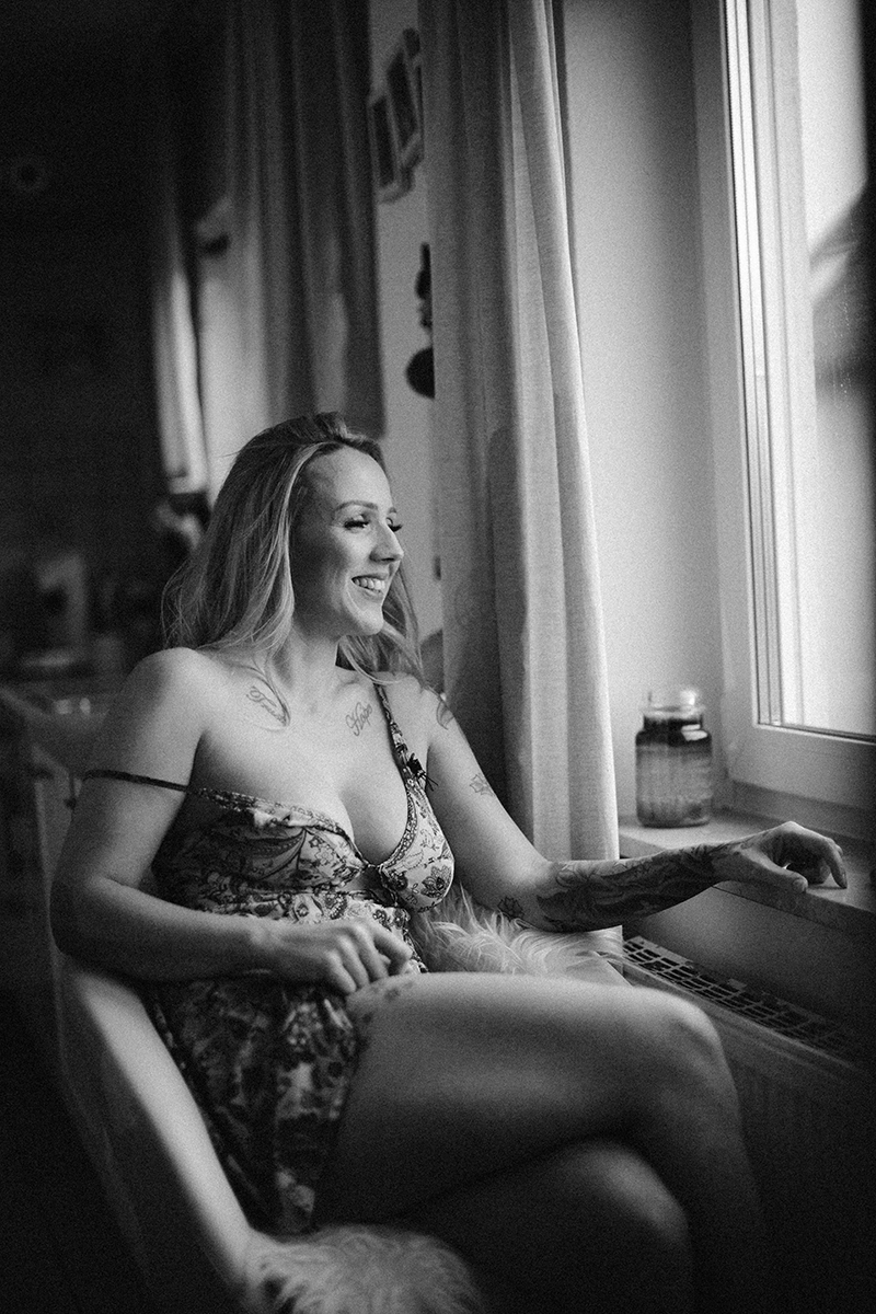 A beautiful tattooed blonde German woman poses for an in-home Niedermohr boudoir photography session wearing a floral night gown in a fur chair in her kitchen in front of a window near Kaiserslautern, Germany