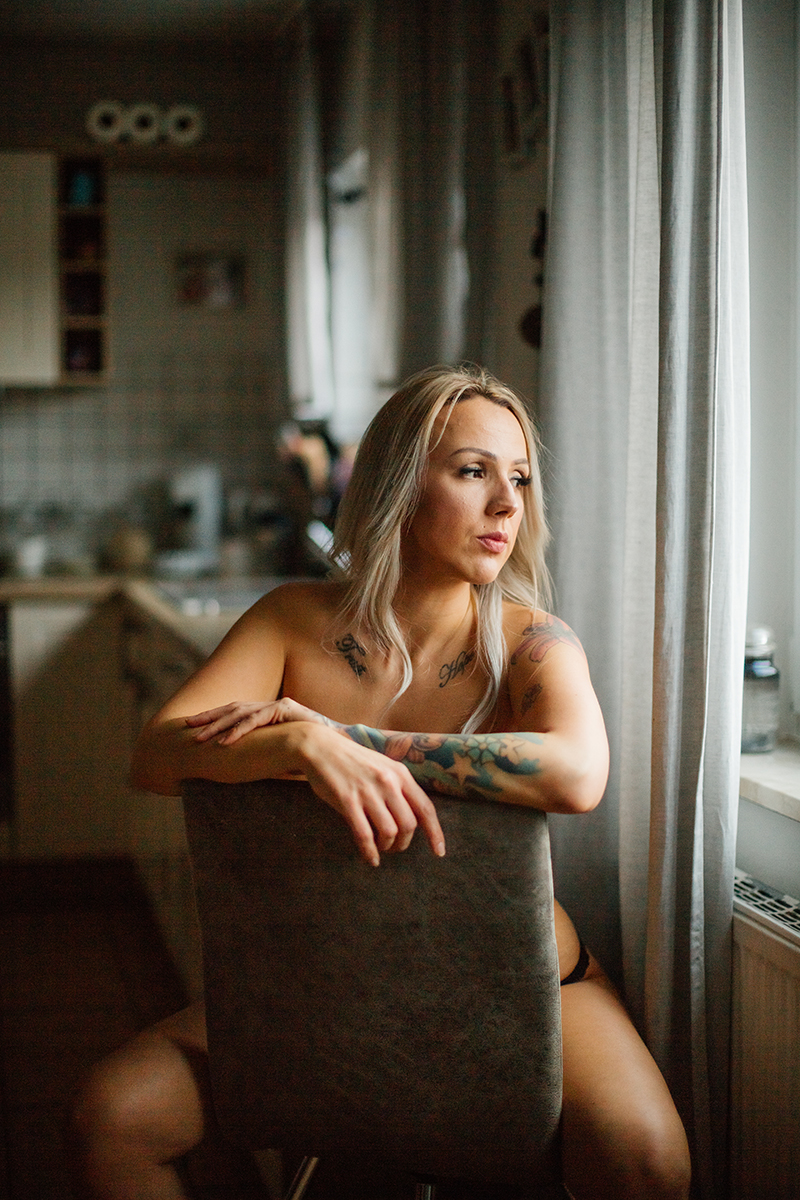 A beautiful tattooed blonde German woman poses topless for an in-home Niedermohr boudoir photography session wearing black underwear in a chair in her kitchen in front of a window near Kaiserslautern, Germany
