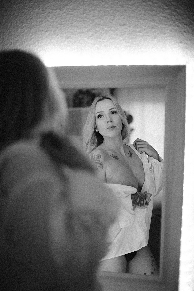 A beautiful tattooed blonde German woman poses topless for an in-home Niedermohr boudoir photography session wearing black underwear and a white button up shirt in front of a mirror in her kitchen near Kaiserslautern, Germany
