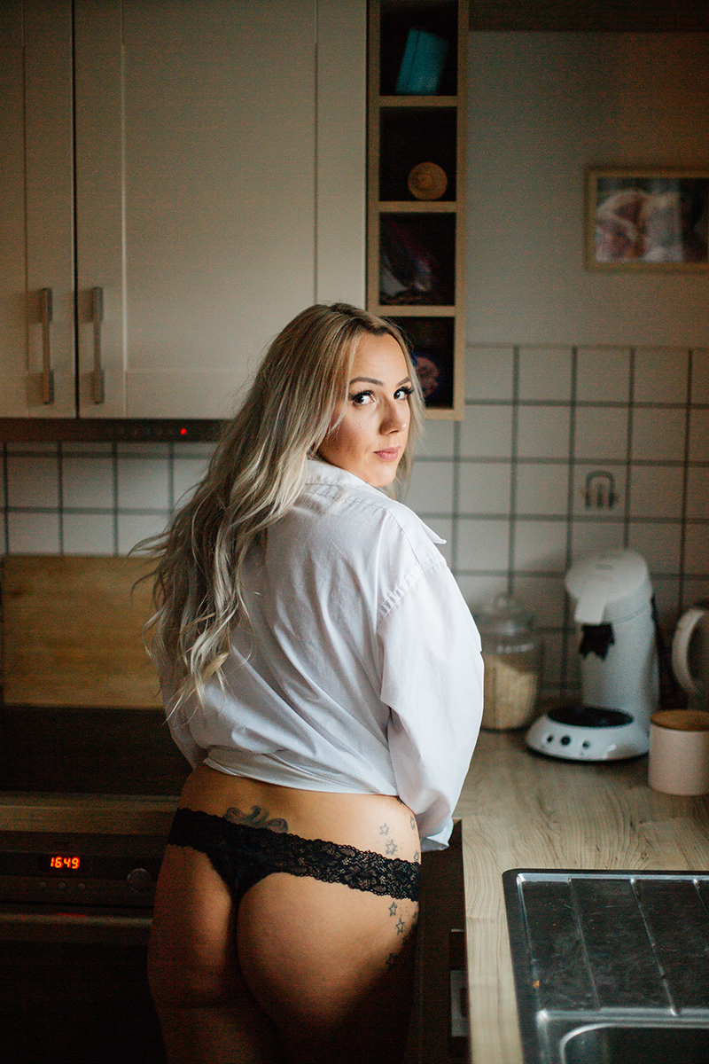 A beautiful tattooed blonde German woman poses topless for an in-home Niedermohr boudoir photography session wearing black underwear and a white button up shirt in front in her kitchen near Kaiserslautern, Germany