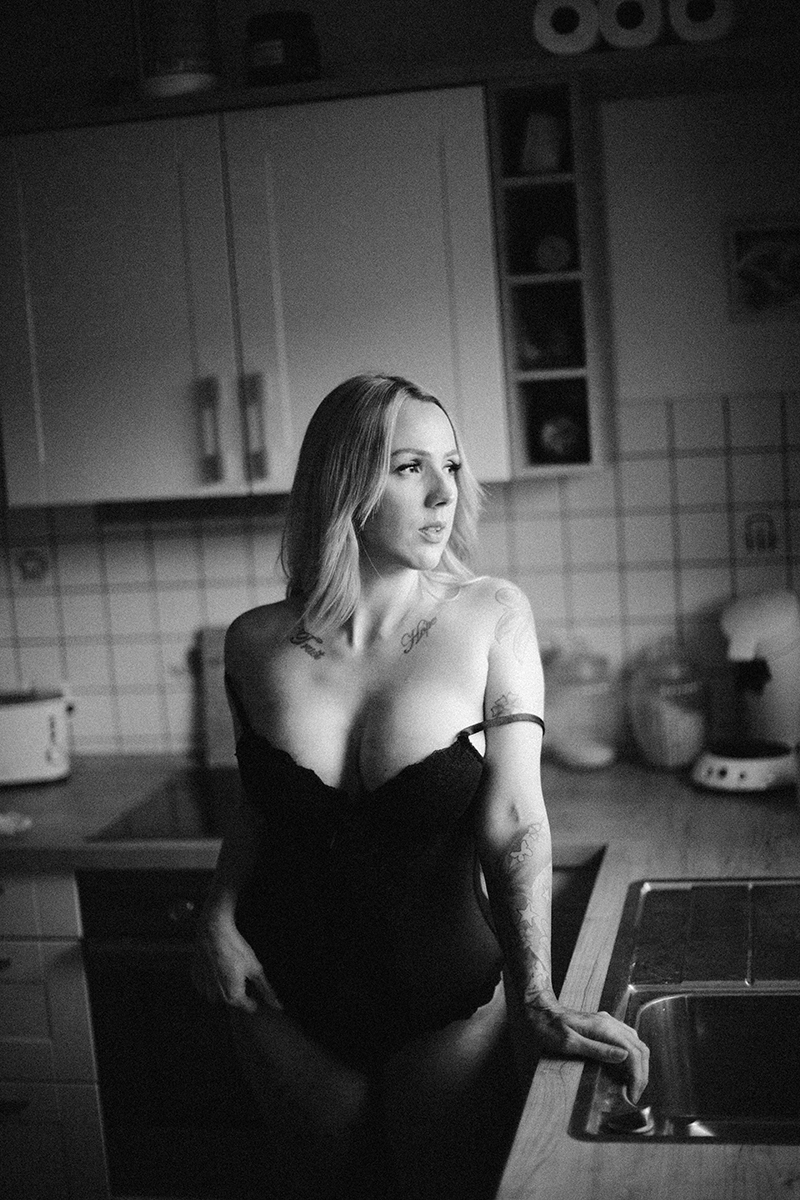 A beautiful tattooed blonde German woman poses for an in-home Niedermohr boudoir photography session wearing black lingerie in her kitchen near Kaiserslautern, Germany