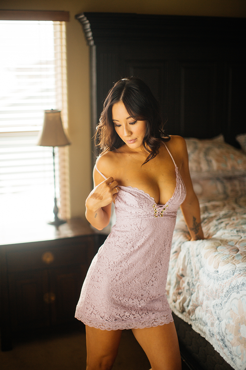 A beautiful brunette woman poses for a Colorado Springs home boudoir photography session wearing light purple lingerie standing next to her bed in Colorado