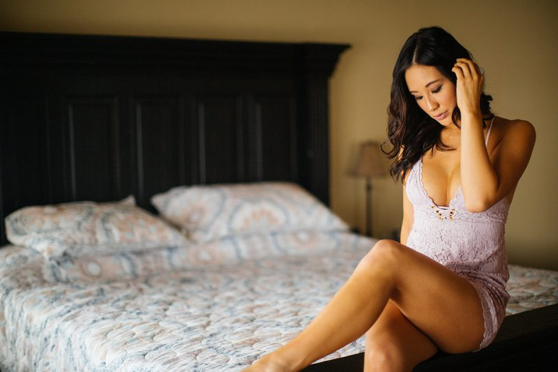 A beautiful brunette woman poses for a Colorado Springs home boudoir photography session wearing light purple lingerie sitting on her bed in Colorado