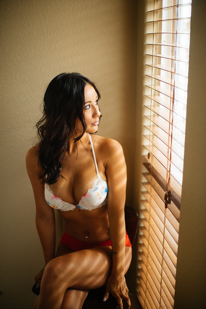 A beautiful brunette woman poses for a Colorado Springs home boudoir photography session wearing a white colorful bra and red underwear sitting on a stool next to a window in Colorado