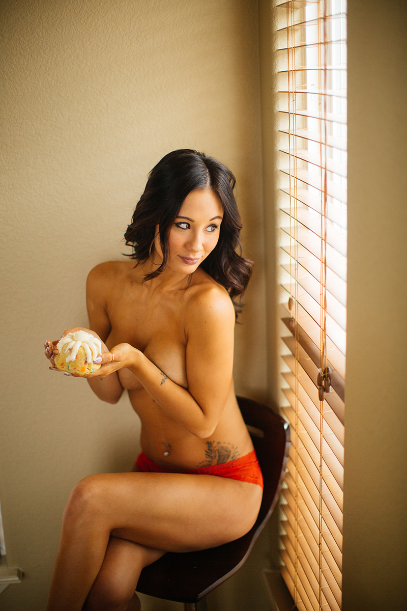 A beautiful brunette woman poses topless for a Colorado Springs home boudoir photography session wearing red underwear sitting on a stool next to a window holding a birthday cupcake in Colorado