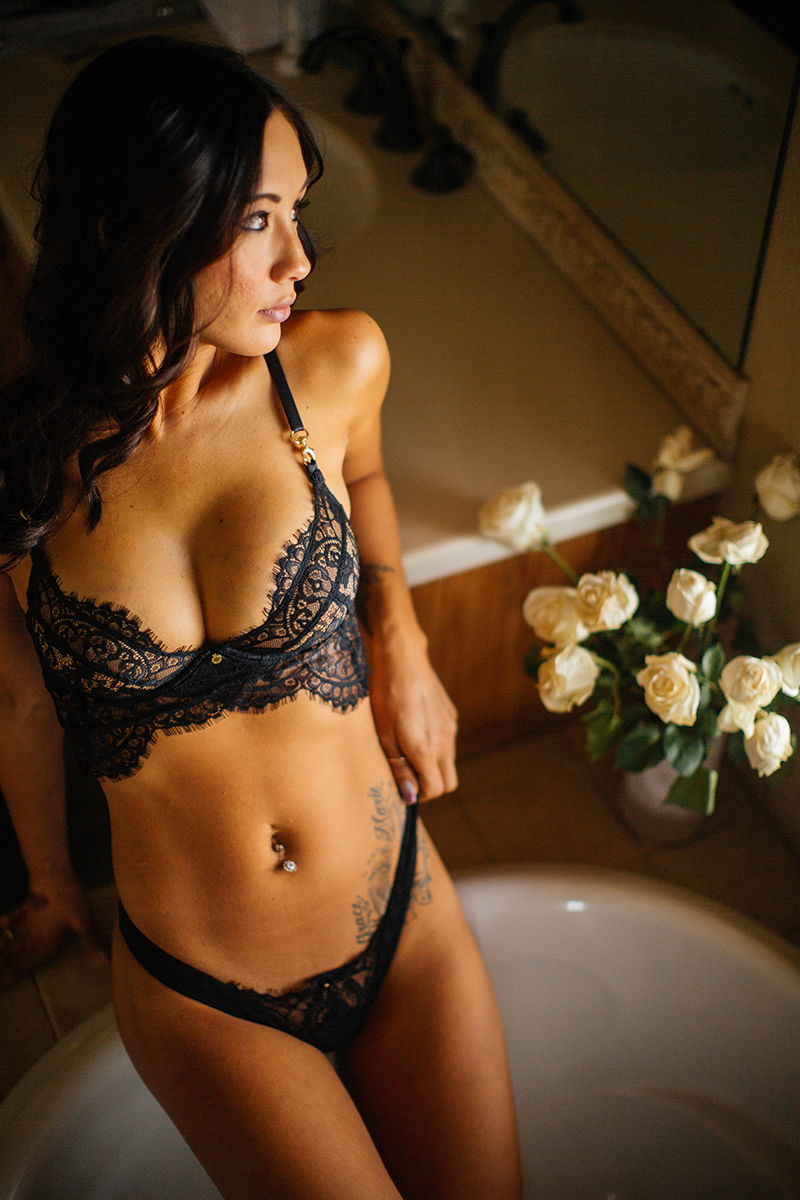 A beautiful brunette woman poses for a Colorado Springs home boudoir photography session wearing a black bra and underwear set standing in a bathtub in her bathroom in Colorado